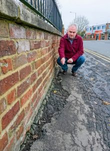 Jeremy Hilton points out the poor state of the footway along Priory Road